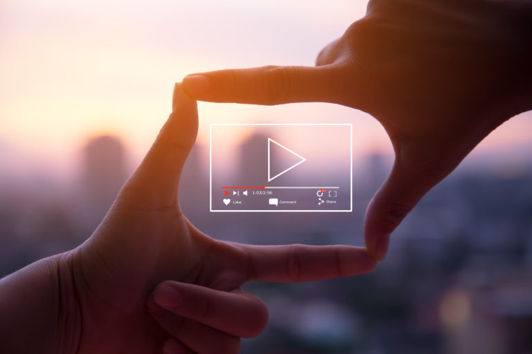 Online live video marketing concept.Photo sign made by human hands on blurred sunset sky as background