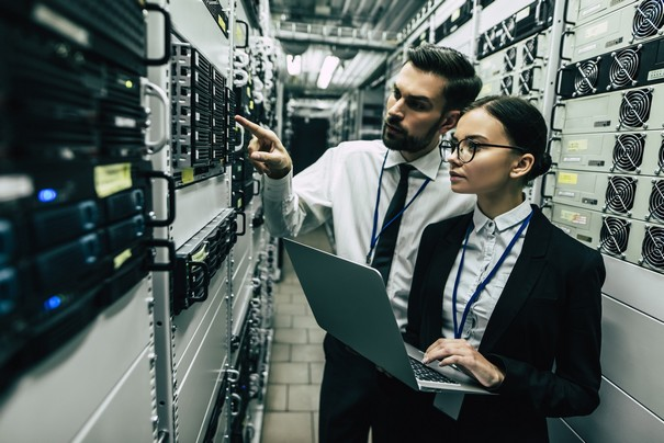 Handsome man and attractive woman are working in data centre with laptop. IT engineer specialists in network server room. Running diagnostics and maintenance. Technicians examining server.