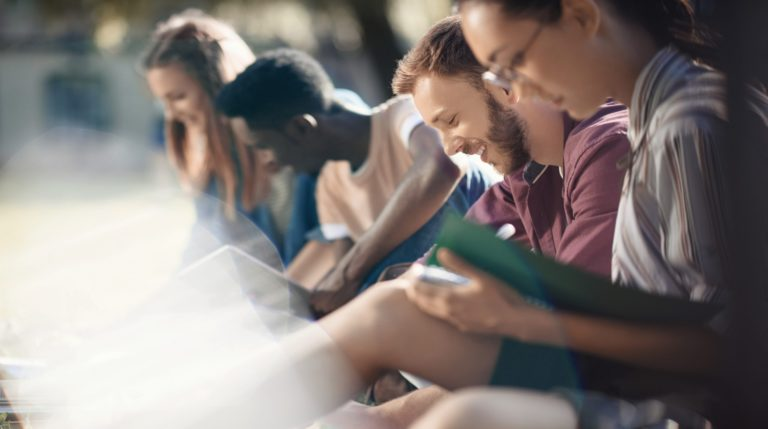 selective focus of happy multicultural students studying with books in park
